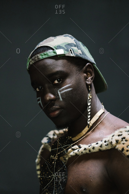 Close up portrait of a young Man in African attire posing against a gray wall