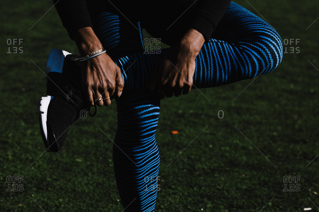Close up of a black athletic woman stretching her legs on a grass field