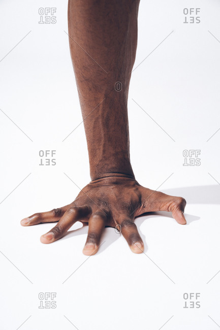 Close up of the strong forearm of a muscular black man while performing push-ups