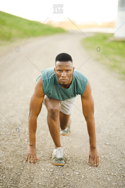 Portrait of an athletic man taking position to start sprinting