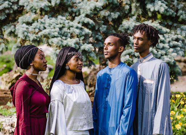 Two young black Muslim men standing opposite of two black Muslim women in Islamic clothing