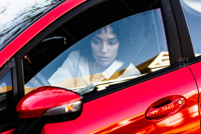 Woman driving a red car and looking through the rear view mirror