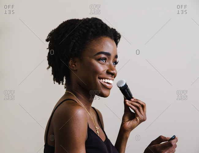 Portrait of a black model smiling and holding a makeup brush in front of a white wall