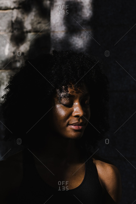 Shadow falling over a woman in a black tank top with her eyes closed