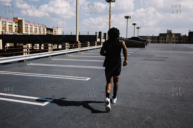 Back side of a man running across a parking lot as part of his exercise