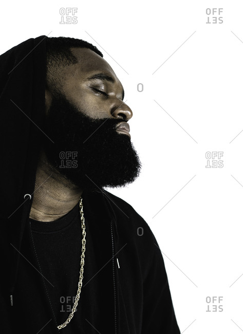 Portrait of a man with a beard and gold chain dressed in a black hoodie
