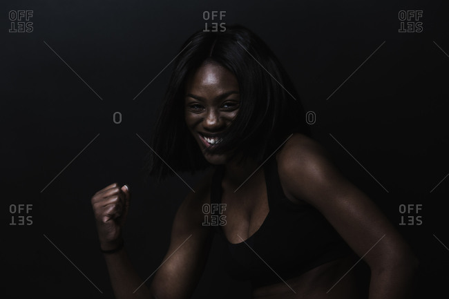 Black woman in an athletic tank top smiling and showing her fist in front of a dark background