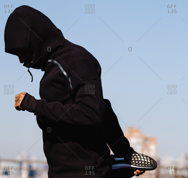 Man in a hoodie stretches out his thigh with the sky in the background