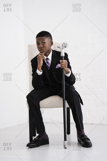 Vertical portrait of a boy in chair posing with hand on chin and a fancy cane looks at the camera