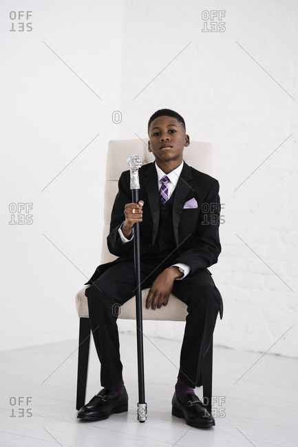 Vertical full length portrait of a boy in chair holding a fancy cane in a black suit looks at the camera