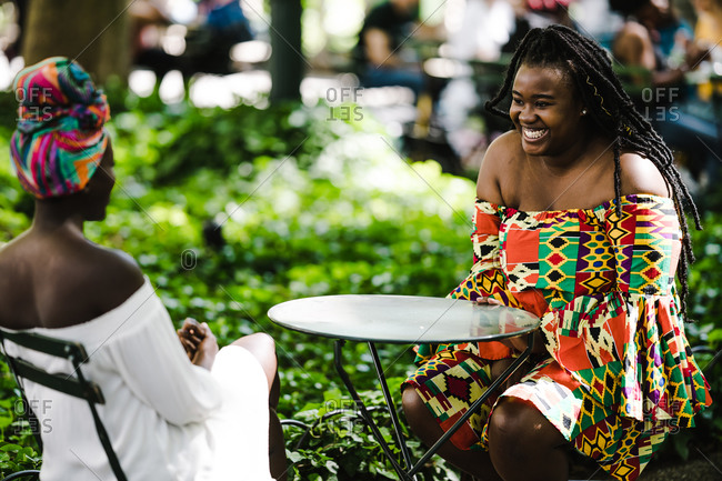 A medium shot of  happy black women sitting outside at a small table