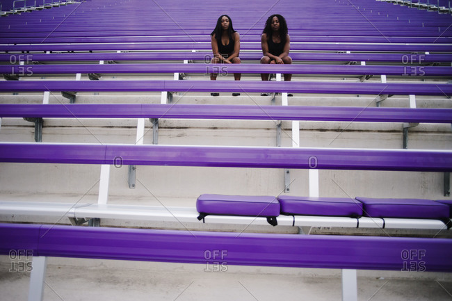 Horizontal shot of two women sitting on the stadium bleachers look at the camera