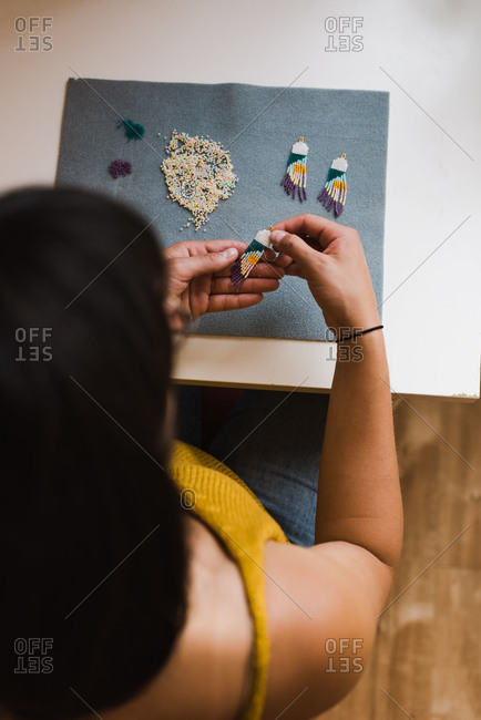 Overhead shot of a mixed race woman making beaded earrings in her home