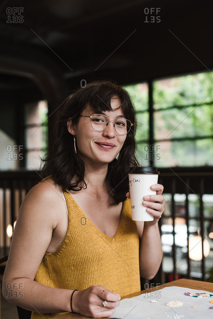 Vertical shot of a mixed race woman sitting at a table and drinking coffee while making jewelry for her business