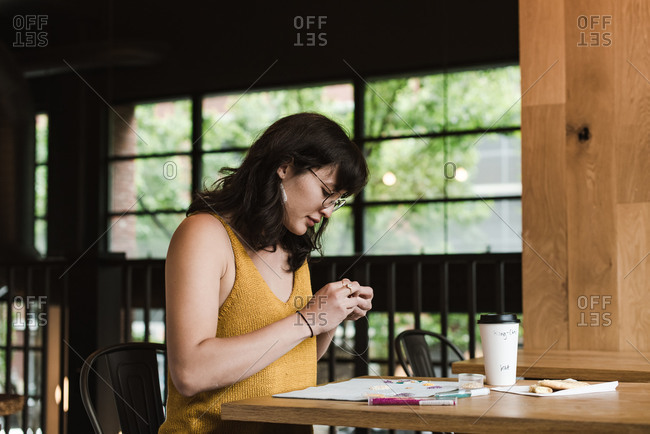 Horizontal shot of a mixed race woman sitting at a table and making jewelry for her business