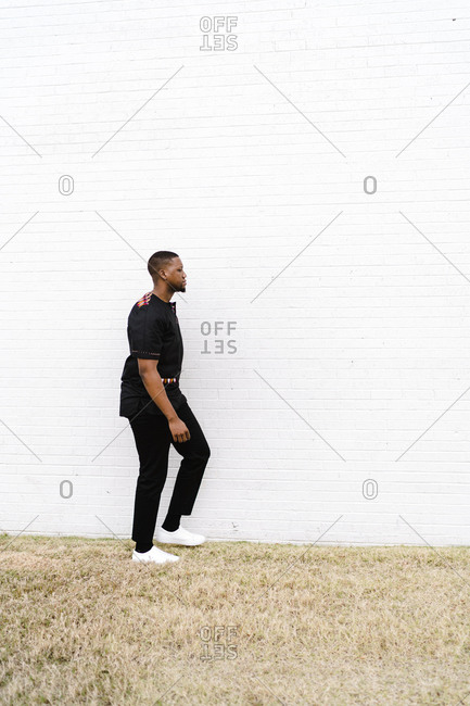 Stylish black man in fashionable clothes walking in front of a white brick wall