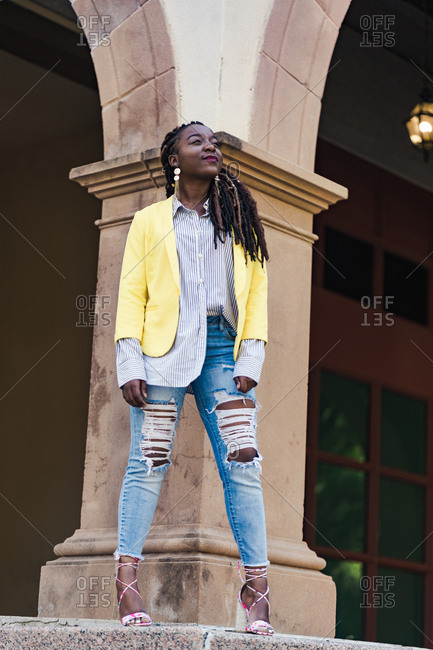Confident young girl with long braided hair posing in front of a column
