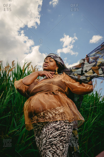 Pregnant Black woman in a field of wheat crops tying a traditional African headwrap around her head