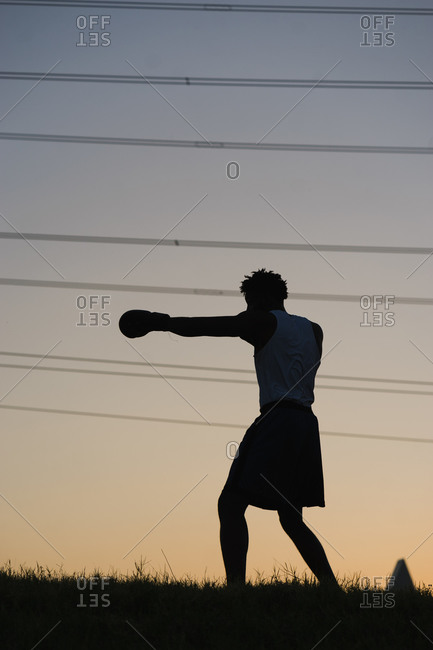 Silhouette of a black man boxing in the evening on a grassy field