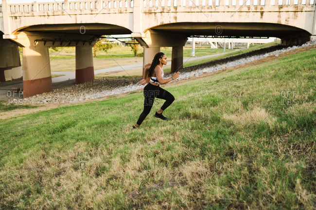 Athletic black woman running up a grassy slope