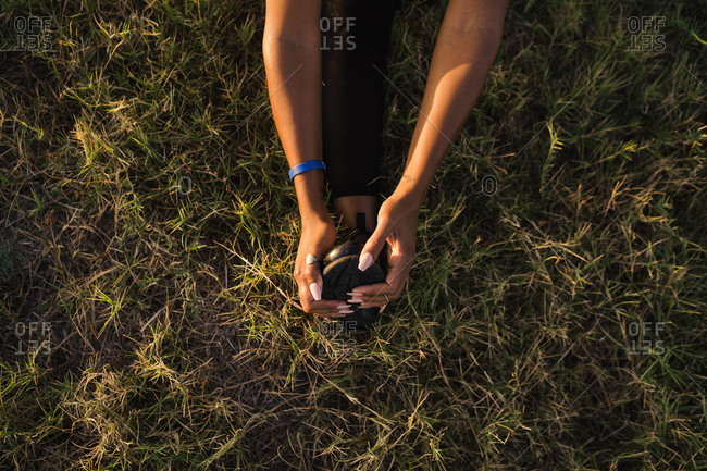 Overhead shot of a black woman stretching her legs in the field