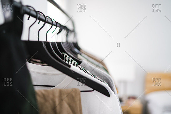 Close up of a clothing rack with men's clothes hanging on hangers