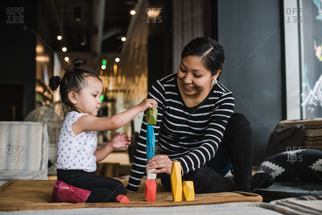 Mother playing wooden blocks with her daughter while sitting on a mat