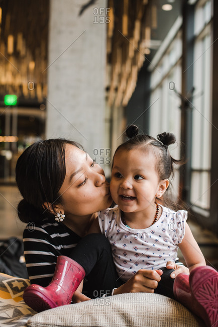 Vertical portrait of a mother kissing her daughter on the cheeks