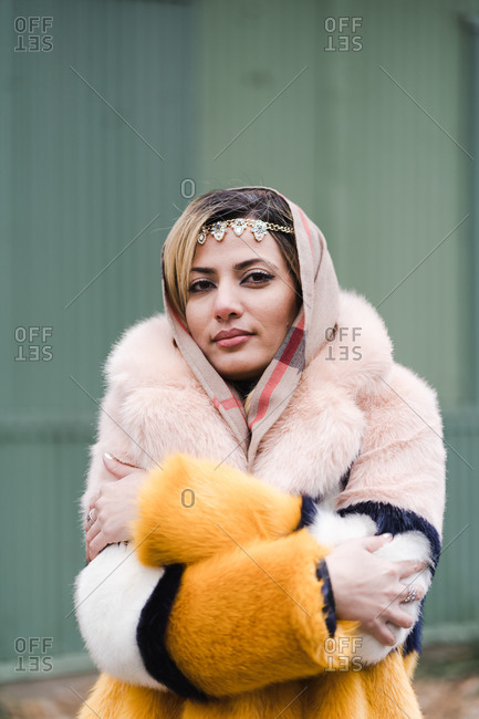 Stylish Muslim woman clutching her beautiful fur coat with closed eyes
