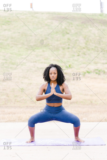 Strong focused woman squatting and performing yoga outdoors