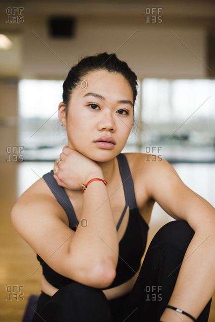Confident woman sitting and posing in a yoga studio