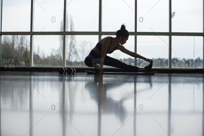 Landscape shot of a young dancer stretching on the gym floor