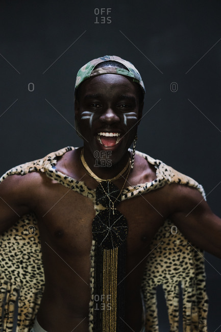 Portrait of a laughing young man in African attire standing with wide arms against a gray wall