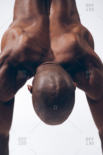 Close up of the back of a muscular black man performing a handstand