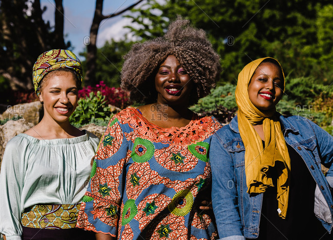 A group of three black Muslim women smiling and standing together