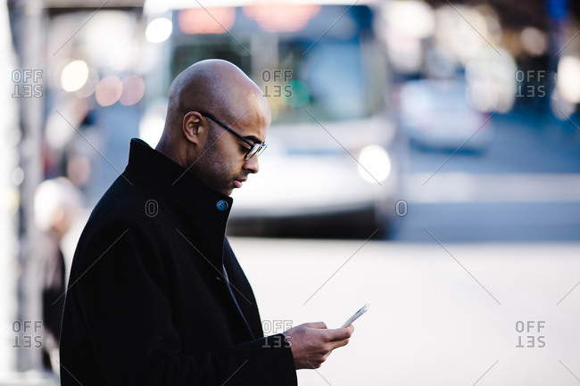 Side view of a bald man wearing a heavy coat scrolls through a phone while standing outdoors