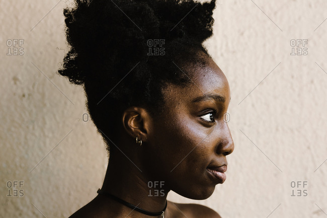 Close up of a black woman with two afro puffs standing in front of a wall