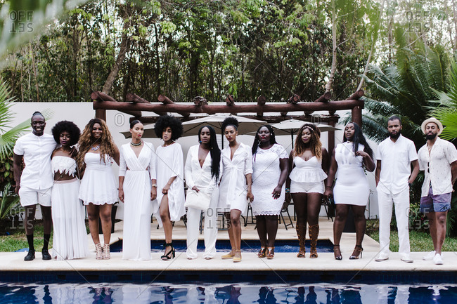 A group of black men and women wearing white outfit pose next to a pool with trees in the background