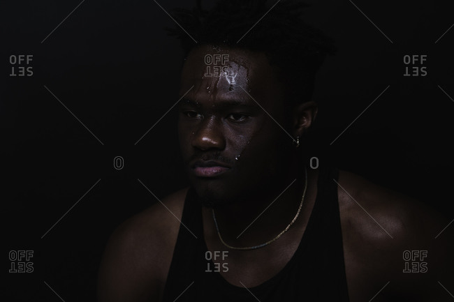 Close up portrait of a black man with sweat dripping down his face after working out