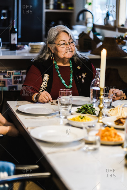 Vertical shot of a joyous american Indian and alaska native elder sitting at the head of the dinner table for a meal