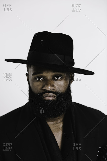 Close up portrait of a man in a black hat and beard with a white background