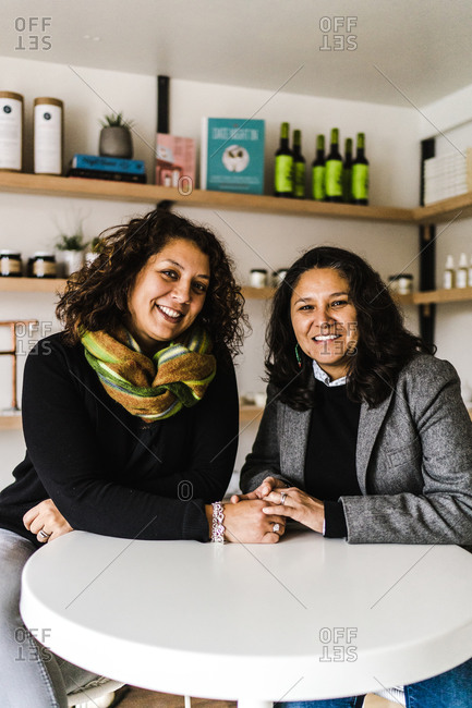 Vertical portrait of a joyous lesbian couple sitting close holding hands at a restaurant table smile at the camera