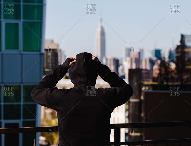 Man in a hoodie standing next to the fence overlooking a balcony