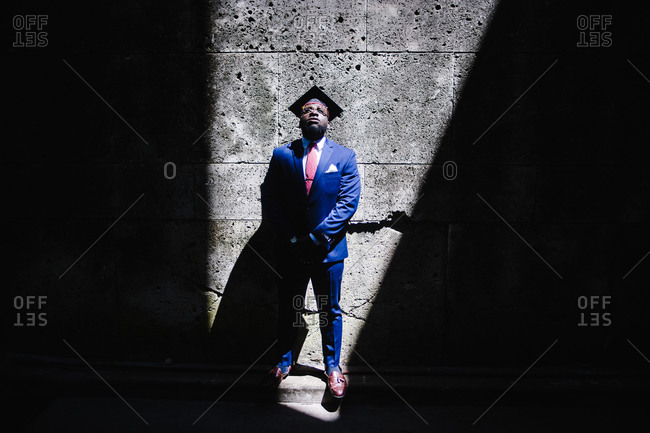 Horizontal portrait of a man in velvet suit wearing a graduation hat leans against a wall in sliver of light