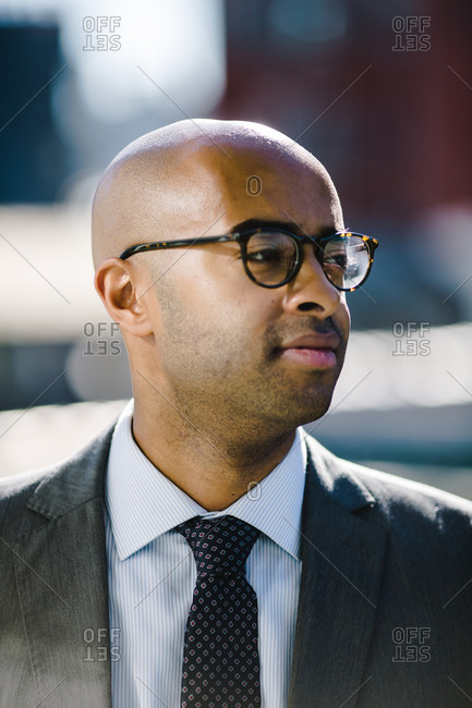 Portrait of a bald black man in a suit and glasses looking off into the distance
