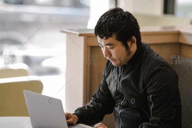 A side profile shot of an asian man working on a laptop at a table