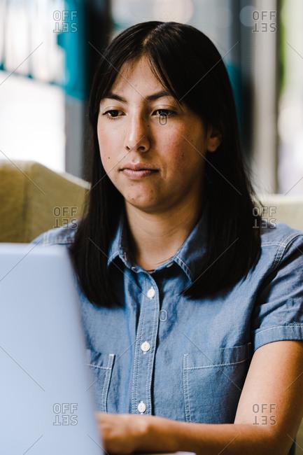 A close up portrait shot of a Hispanic woman using a computer