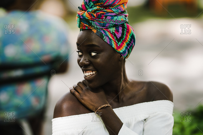 A portrait shot of a smiling African woman wearing a colorful headwrap and a white off-shoulder blouse