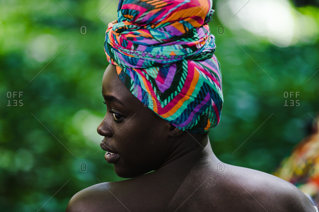 A side profile close up shot of a black woman from behind wearing a colorful headwrap