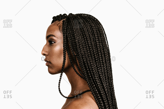 A side profile shot of a young black woman with long braid extensions